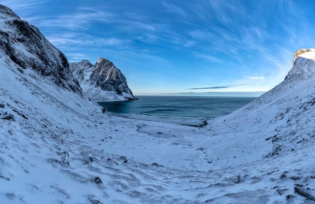 Strand bedeckt im schnee durch die berge in den lofoten-inseln, norwegen