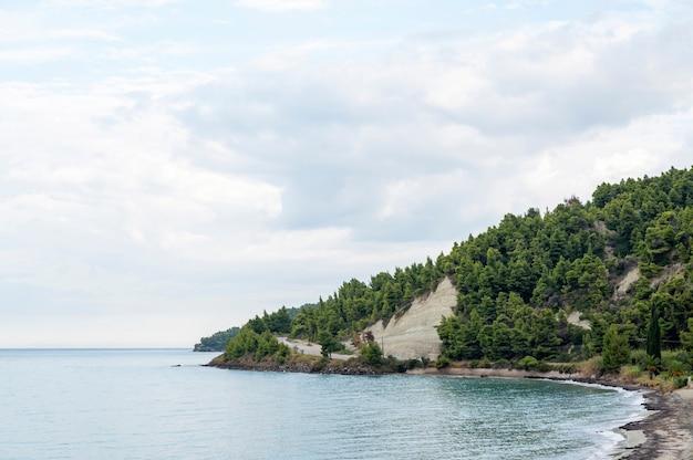 Strand, blaues wasser, hügel und straße bei bewölktem wetter in griechenland