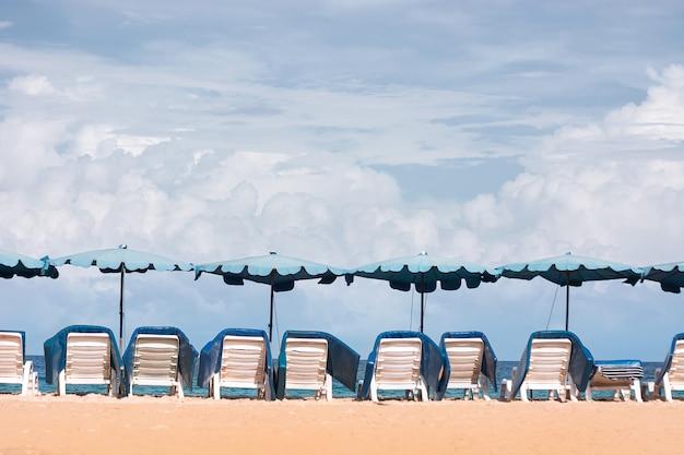 Strand blue chair, sonnenschirm am strand und das leuchtend grüne meer, an einem guten tag.