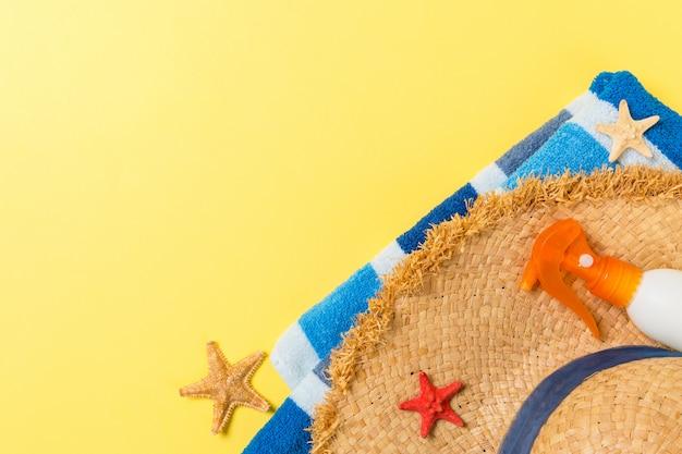 Strand flach legen zubehör mit kopierraum. gestreiftes blaues und weißes handtuch, muscheln, staw sunhat und eine flasche sonnencreme auf gelbem hintergrund. sommerferienkonzept