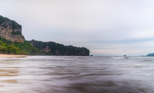 Strand meer sonnenuntergang oder sonnenaufgang mit bunten himmel und wolken mit sonnenlicht in der dämmerung langzeitbelichtung