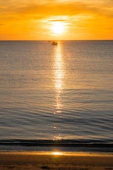 Strand, meer während des sonnenaufgangs der sommersaison morgens mit fischerboot des schattenbildes.