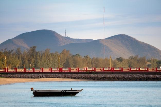 Strand, meer während des sonnenaufgangs der sommersaison morgens mit kleinem fischerboot.