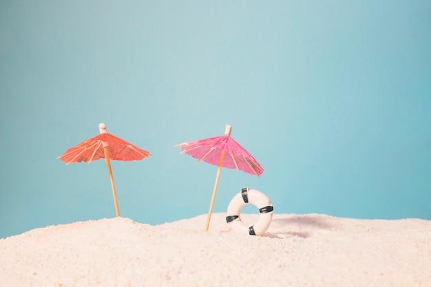 Strand mit roten sonnenschirmen und rettungsring
