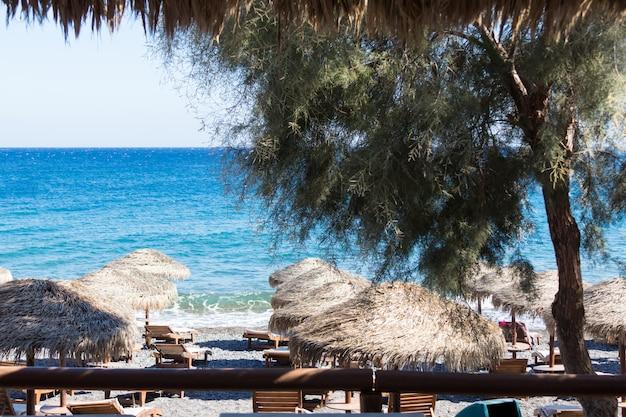 Strand mit sonnenschirmen und liegestühlen am meer in santorini