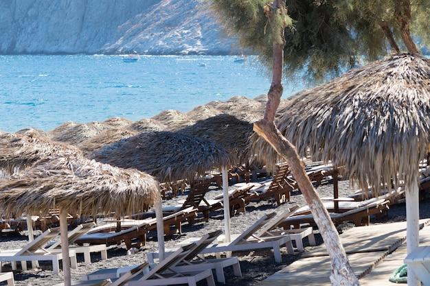 Strand mit sonnenschirmen und liegestühlen in santorini