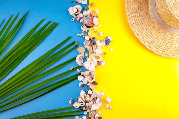 Strand see urlaub konzept zusammensetzung hut, palmblatt, muschel auf blau, gelbe farbe. nahansicht. draufsicht. selektiver weichzeichner. textkopierplatz.