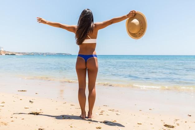 Strand-sommerferienfrau im glücklichen freiheitskonzept mit ausgestreckten armen. lateinamerikanische sexy frau, die weißen bikini mit strohhut in den händen trägt