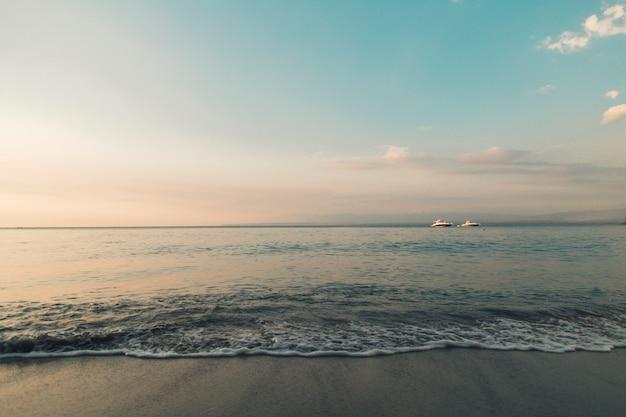 Strand und ruhiger ozean in den sonnenunterganglichtern