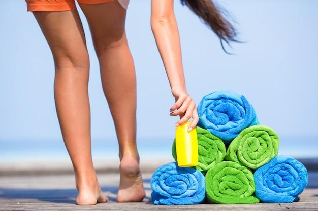 Strand- und sommerferienzubehörkonzept - nahaufnahme von bunten tüchern, von hut, von tasche und von sunblock