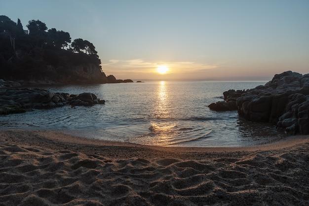 Strand von sa boadella bei sonnenaufgang