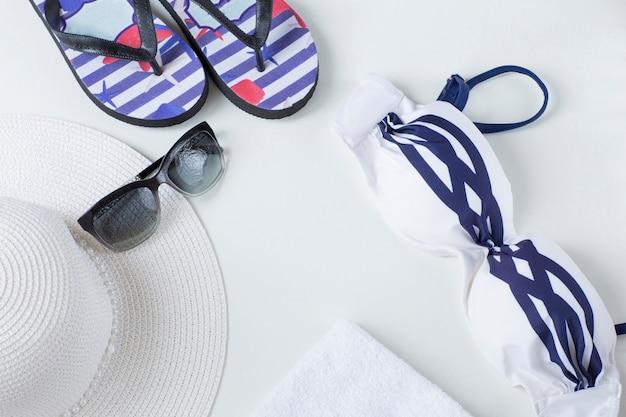 Strandartikel mit strohhut, flip flops, handtuch und sonnenbrille, ansicht von oben. ferienkonzept mit marinethema