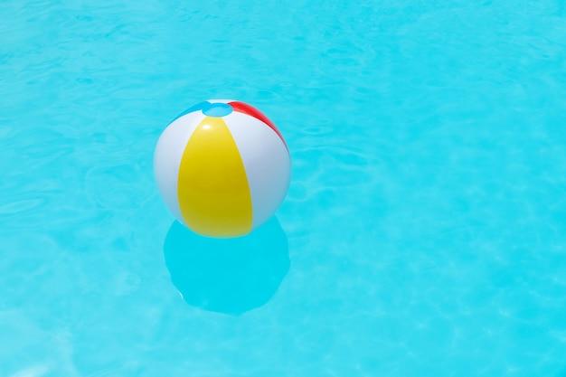 Strandball, der auf der wasseroberfläche eines schwimmbades schwimmt