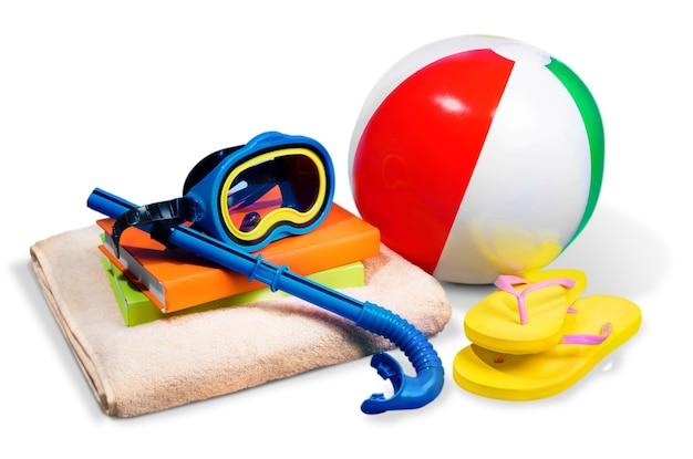 Strandball mit flip-flops und strandzubehör auf weißem hintergrund