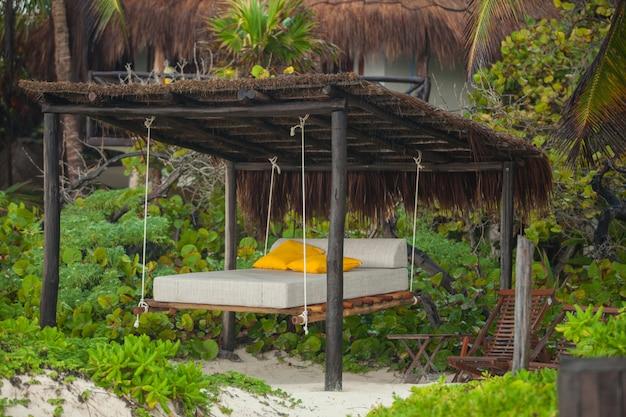 Strandbetten unter den bäumen am tropischen exotischen weißen strand