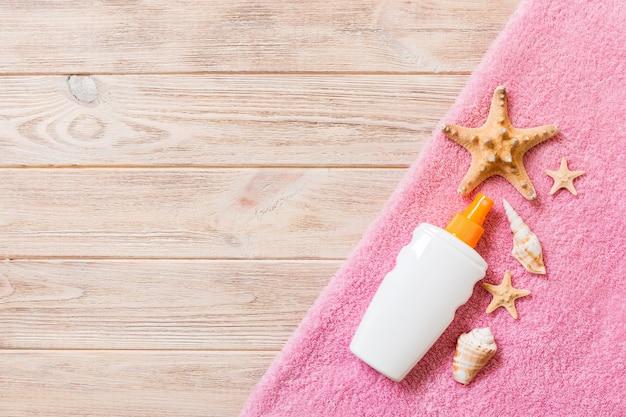 Strandflaches zubehör mit kopienraum. rosa handtuch, seestern und eine flasche sonnencreme auf holzhintergrund. sommerferienkonzept.