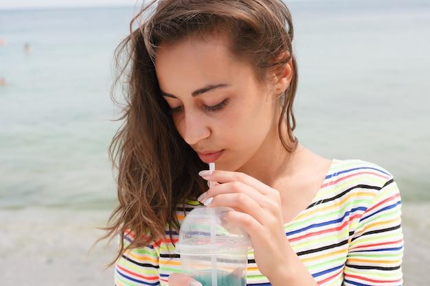 Strandfrau, die kaltes getränkgetränk trinkt und spaß bei der strandparty hat. weibliches baby im bikini, das eistee, cola oder alkoholisches getränk genießt, lächelt glückliches lachen und schaut in die kamera. schönes gemischtrassiges mädchen