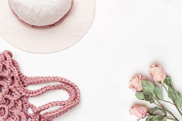 Strandfrauenhut mit breiten klappen aus baumwolle, fasfionrosa strandtasche und rosen auf hellem hintergrund. urlaub und urlaubskonzept. draufsicht. flach liegen.