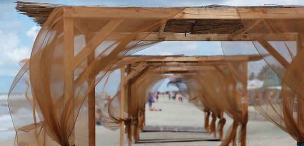 Strandhallen mit braunen vorhängen, die im wind flattern.