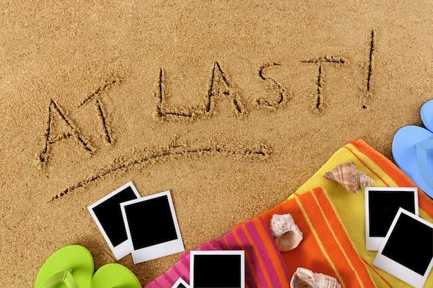 Strandhintergrund mit den wörtern endlich! in sand geschrieben