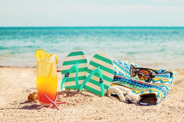 Strandhintergrund mit einem cocktail durch das meer. selektiver fokus