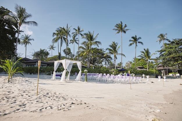 Strandhochzeitsort-küsteneinrichtung, bogen, altar, gang mit blumendekoration