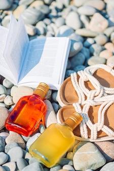 Strandhut auf geöffnetem buch mit sonnencreme und schuhen am kieselstrand