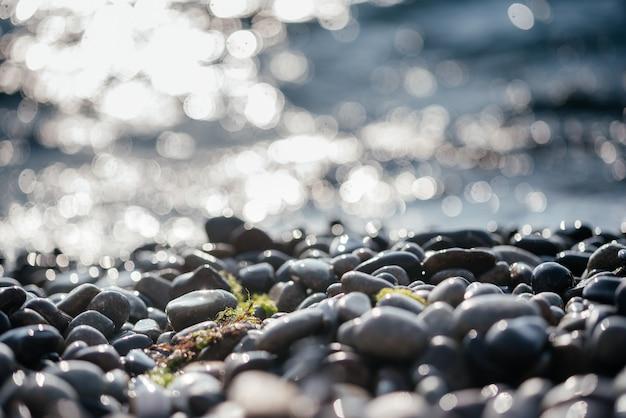 Strandkiesel mit funkelnden sonnenbokeh und schäumenden meereswellen