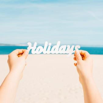 Strandkonzept mit den händen, die feiertagsbuchstaben halten