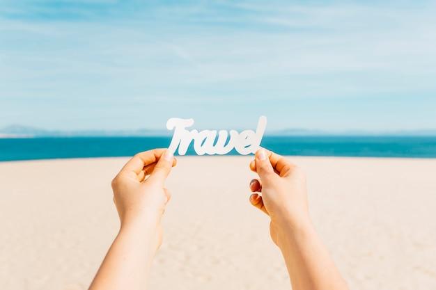 Strandkonzept mit den händen, die reisebuchstaben halten