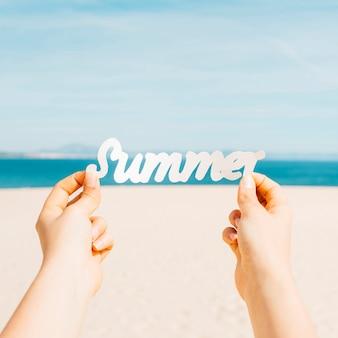 Strandkonzept mit den händen, die sommerbuchstaben halten