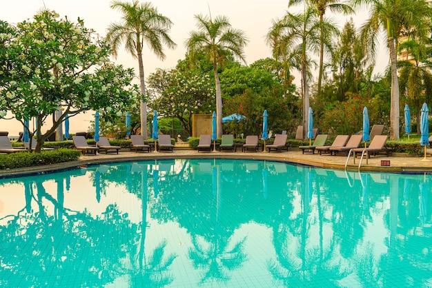 Strandkorb oder poolbett mit sonnenschirm um den pool zur sonnenuntergangszeit