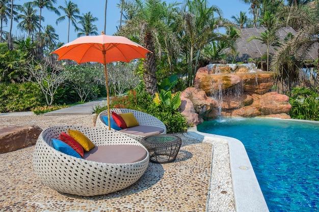Strandkorb und sonnenschirm am tropischen strand in der nähe des swimmingpools am sonnigen tag, thailand. natur- und reisekonzept