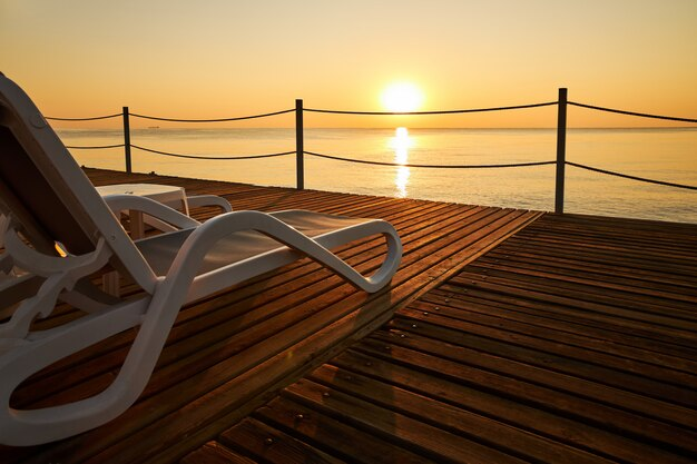 Strandliege steht auf einem hölzernen pier vor dem hintergrund eines ruhigen meeres und der aufgehenden sonne