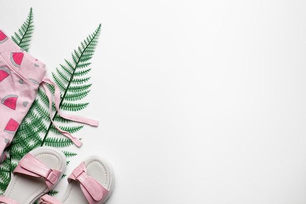 Strandmode mädchen konzept shorts und sandalen auf weißem hintergrund mit tropischen palmblättern flach la...