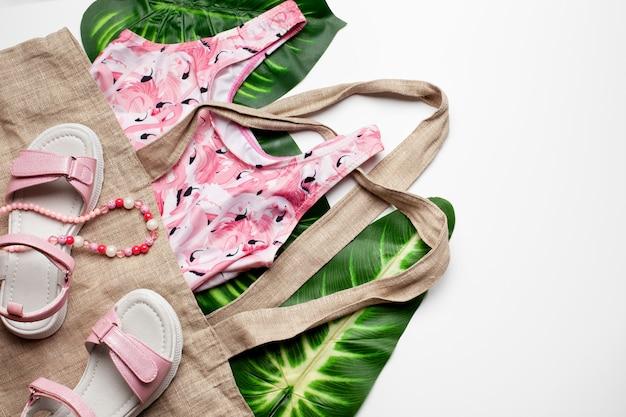 Strandmode mädchenkleidung und accessoires auf weißem hintergrund mit tropischen palmblättern flach t...