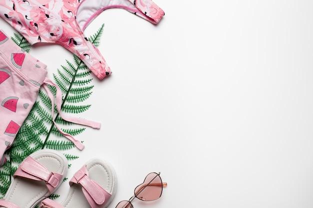 Strandmode mädchenkleidung und accessoires auf weißem hintergrund mit tropischen palmblättern flach ...