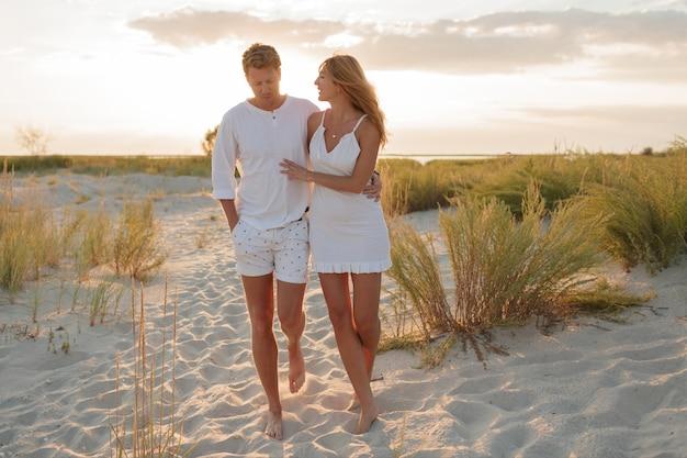 Strandpaar, das barfuß auf sand bei sonnenuntergang spazieren geht flitterwochen.