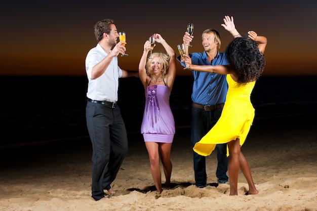 Strandparty mit freunden, die mit getränken tanzen
