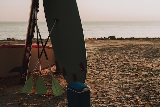 Strandparty. surfs und paddel auf sand.
