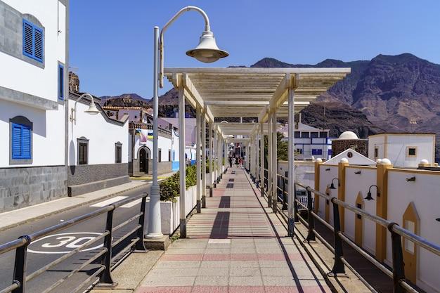 Strandpromenade mit kleinen weißen häusern in leuchtenden farben und hohen bergen. agaete gran canaria. spanien.
