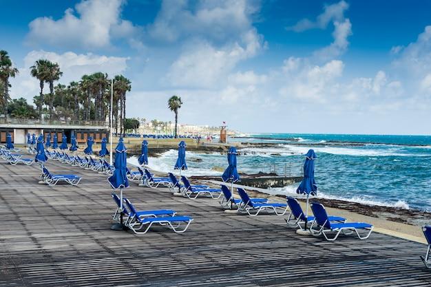Strandpromenadenstrand mit liegestühlen, blauen sonnenliegen am strand