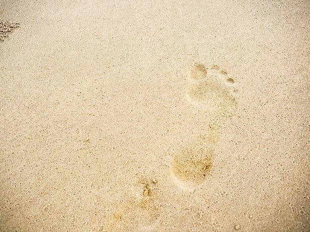 Strandsandabdrücke mit kopienraum. schließen sie den menschlichen fußabdruck vom barfußlaufen auf dem sandstrand-hintergrund. reise, sommerhintergrundkonzept.