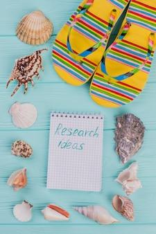 Strandsandalen mit muscheln auf blauem schreibtisch. recherche-ideen auf notizblock in der mitte.