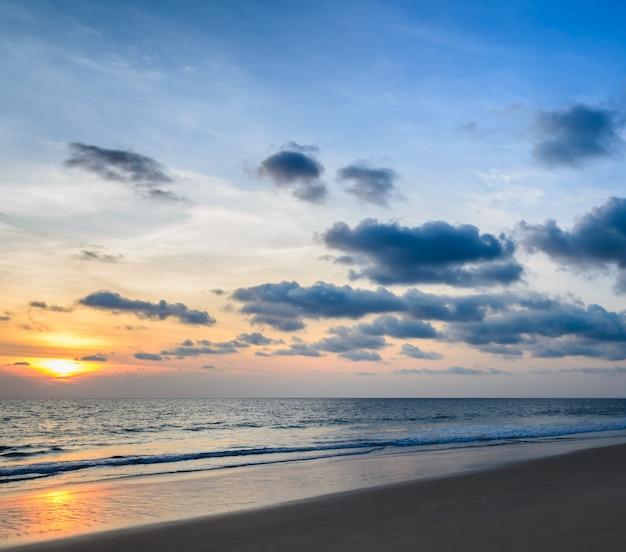 Strandsonnenuntergang mit schönen cloudscape skylinen