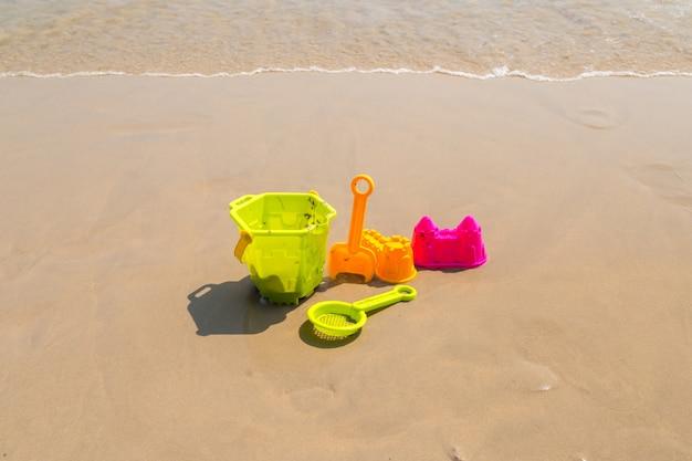 Strandspielzeug der kinder - eimer, spaten und schaufel auf sand an einem sonnigen tag