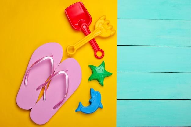 Strandspielzeug für kinder, flip-flops auf gelbem, blauem holz