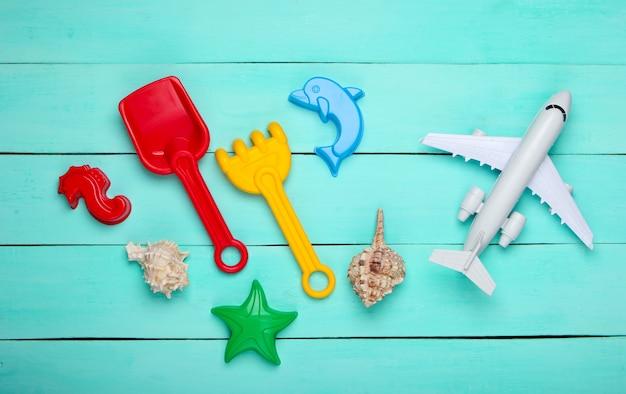 Strandspielzeug für kinder, flugzeugfigur, muscheln auf blauem holz