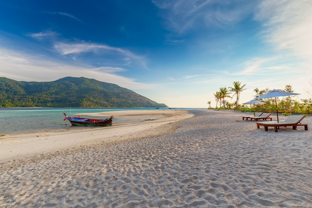 Strandstühle, regenschirm und palmen auf dem schönen strand für feiertage und entspannung in koh lipe-insel, thailand