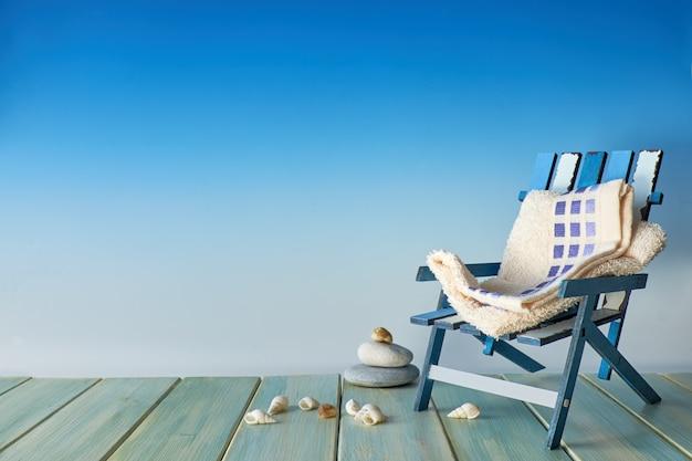 Strandstuhl auf hölzerner terrasse mit meer schält küstendekorationen, copyspace auf blau